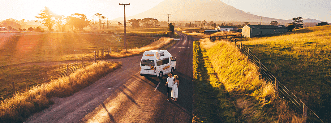 Couple Freedom Camping with a Kuga Campervan during sunset.