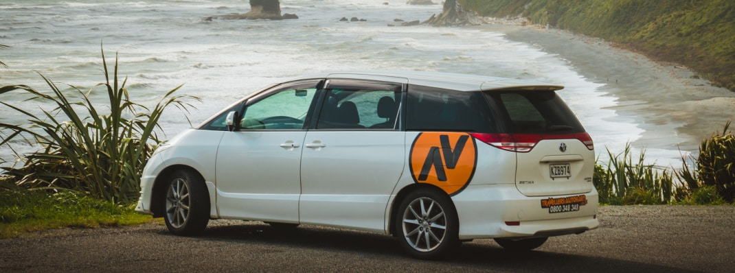 Automatic transmission station wagon parked on cliff overlooking ocean
