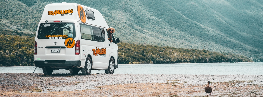 Woman looking at duck outside window of Campervan