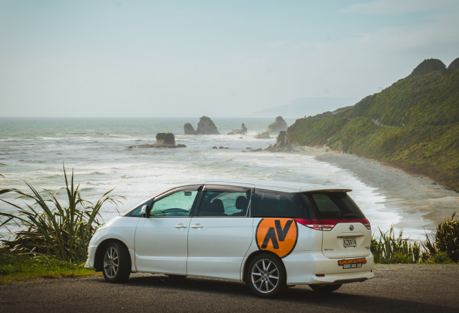 Travellers Autobarn station wagon parked by the ocean in New Zealand