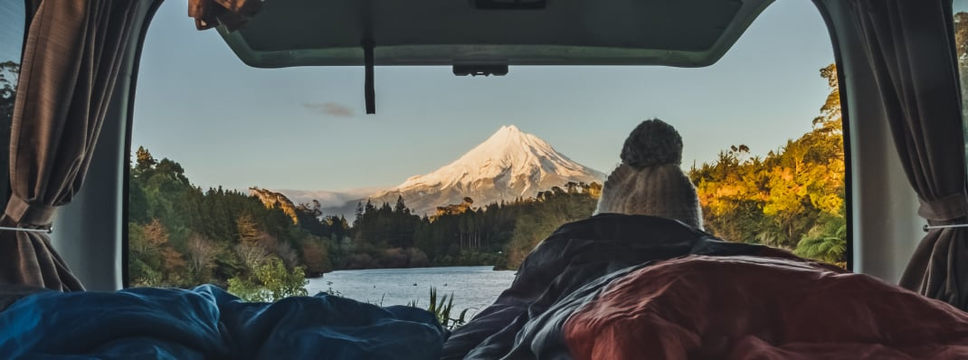 Young woman watching the mountains from the back of her campervam