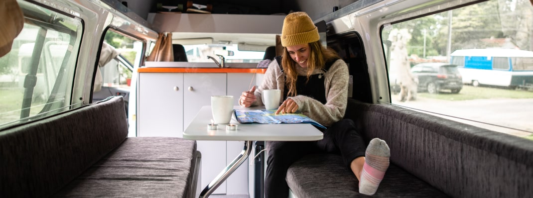 Young woman planning campervan trip with map