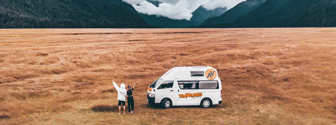 Couple standing in wilderness with their campervan