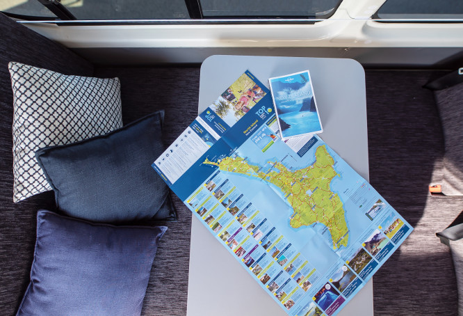 Map of New Zealand and travel itinerary on table in campervan