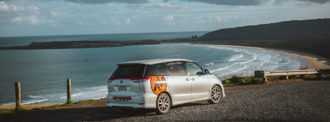 Travellers Autobarn stationwagon parked by a cliff in New Zealand