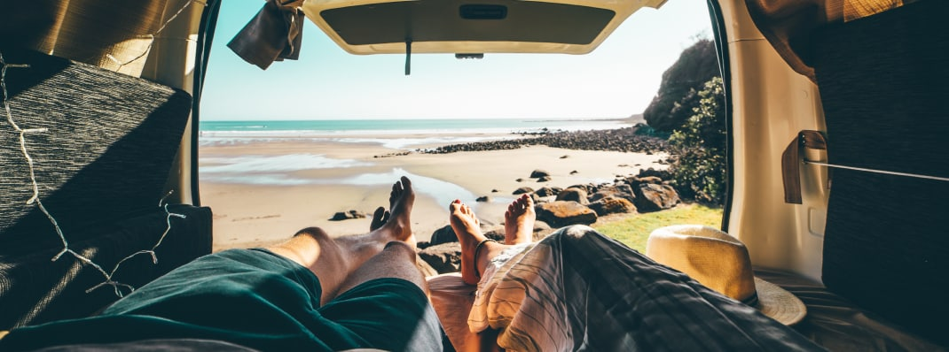 Couple laying in back of campervan by NZ beach