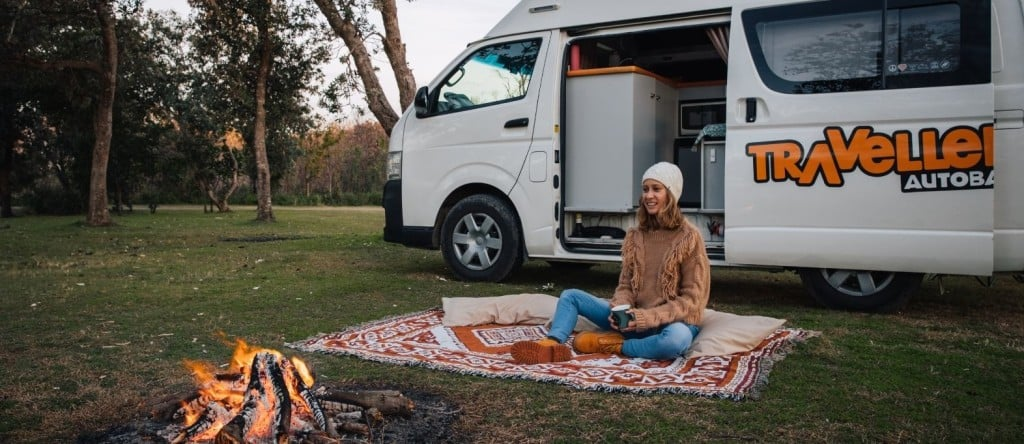 female sitting outside a campervan with a campfire