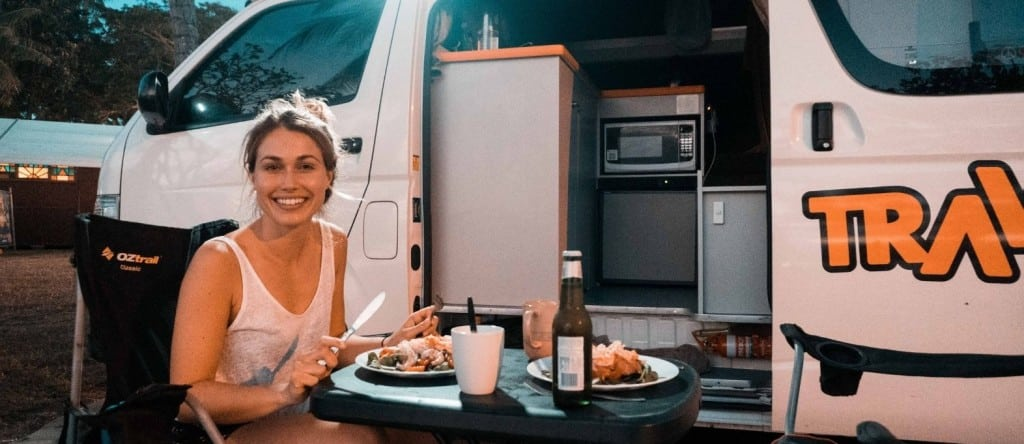 Female eating a meal outside a campervan