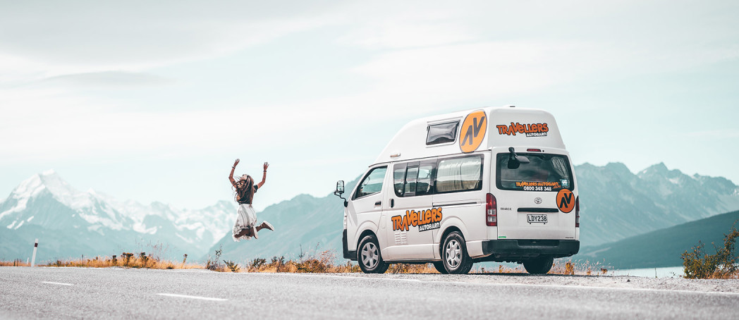 Girl jumping in the air outside a campervan by mountains in New Zealand