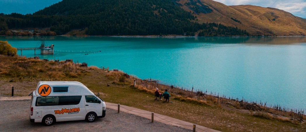 Couple sitting outside a campervan by lake in New Zealand on a road trip