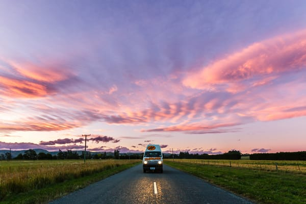 Campervan driving under pink skies - Benefits of Buying a Campervan in New Zealand