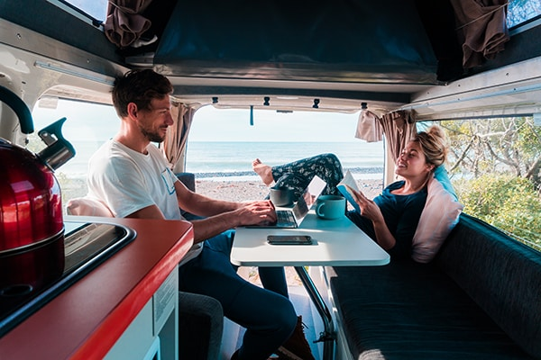 Couple in the back of a campervan Benefits of Buying a Campervan in New Zealand