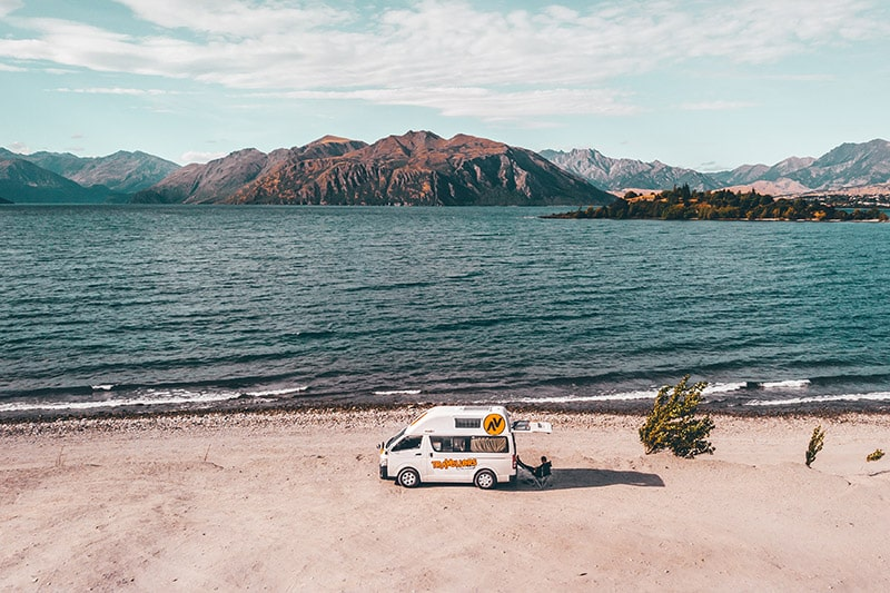 Resting by a campervan by a lake in New Zealand Mechanic Tips For Safe Road Trips NZ